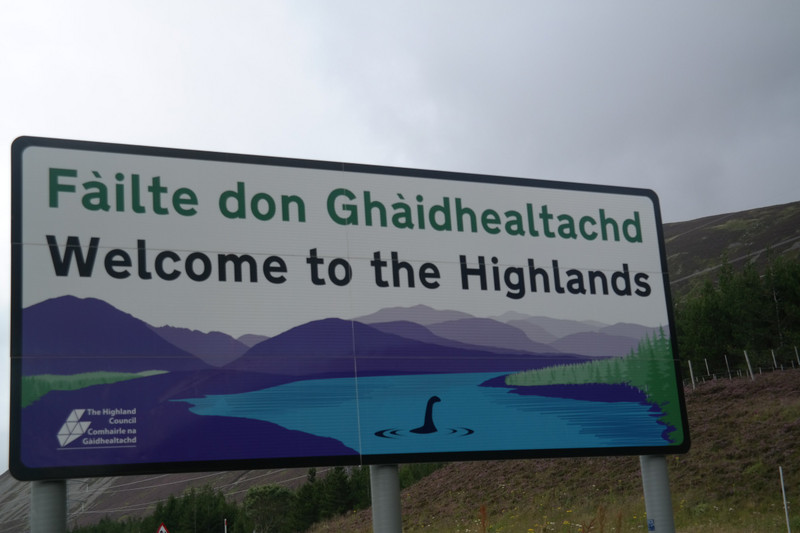 Road sign welcoming visitors to the Highlands. Someone has added a hand-drawn Nessie into the loch.