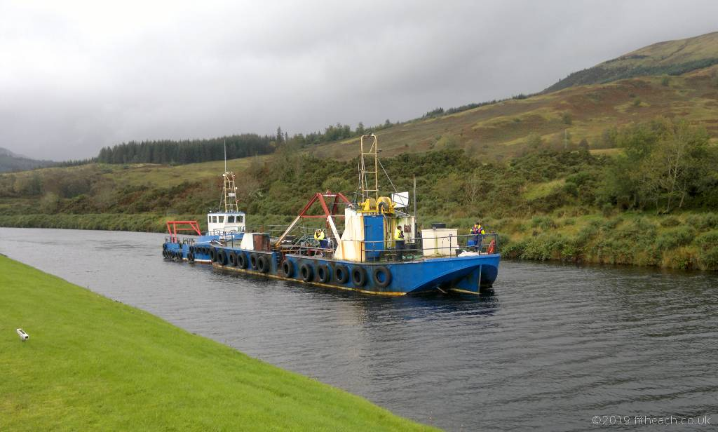 Two boats on the Caledonian Canal. One boat appeared to be towing the other.