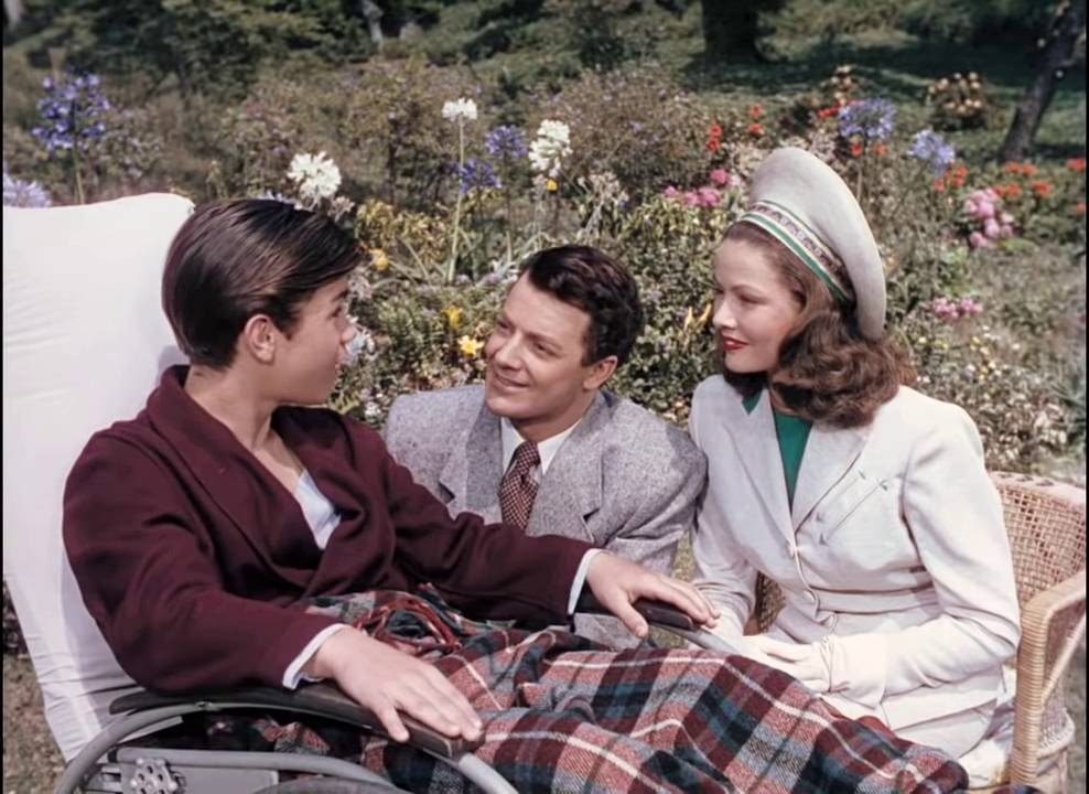 Danny (Darryl Hickman) is talking to Richard (Cornel Wilde) and Ellen (Gene Tierney) in Leave Her to Heaven (1945).